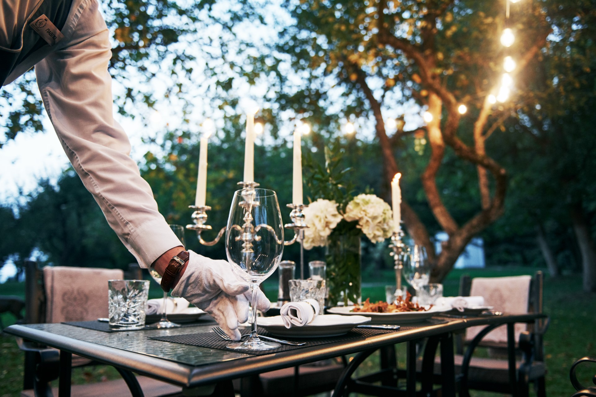 waiter with white gloves preparing a table for dinner in a garden