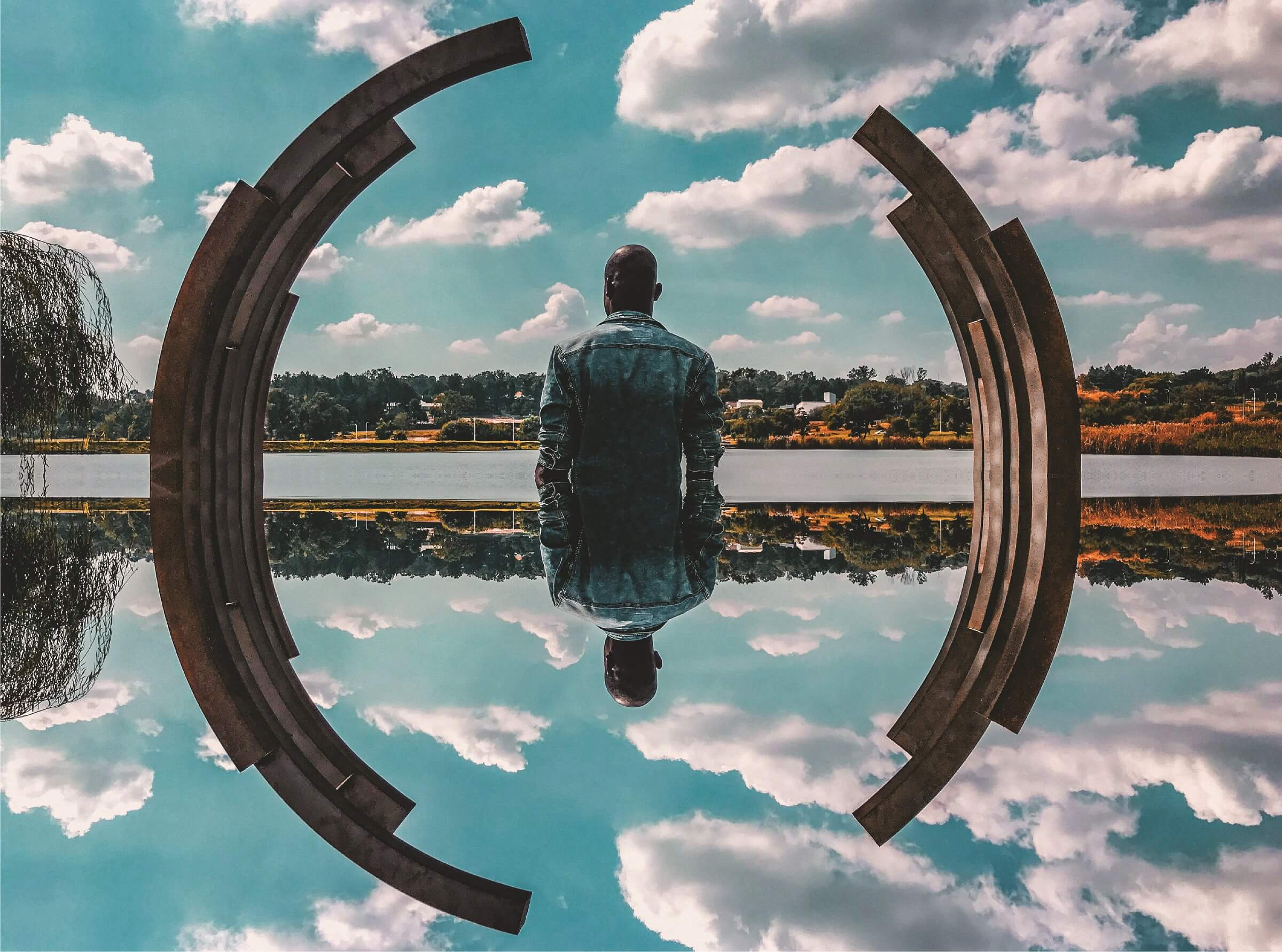 black man standing in the middle of a circle surrounded by a lake and the sky σεμινάρια Photoshop