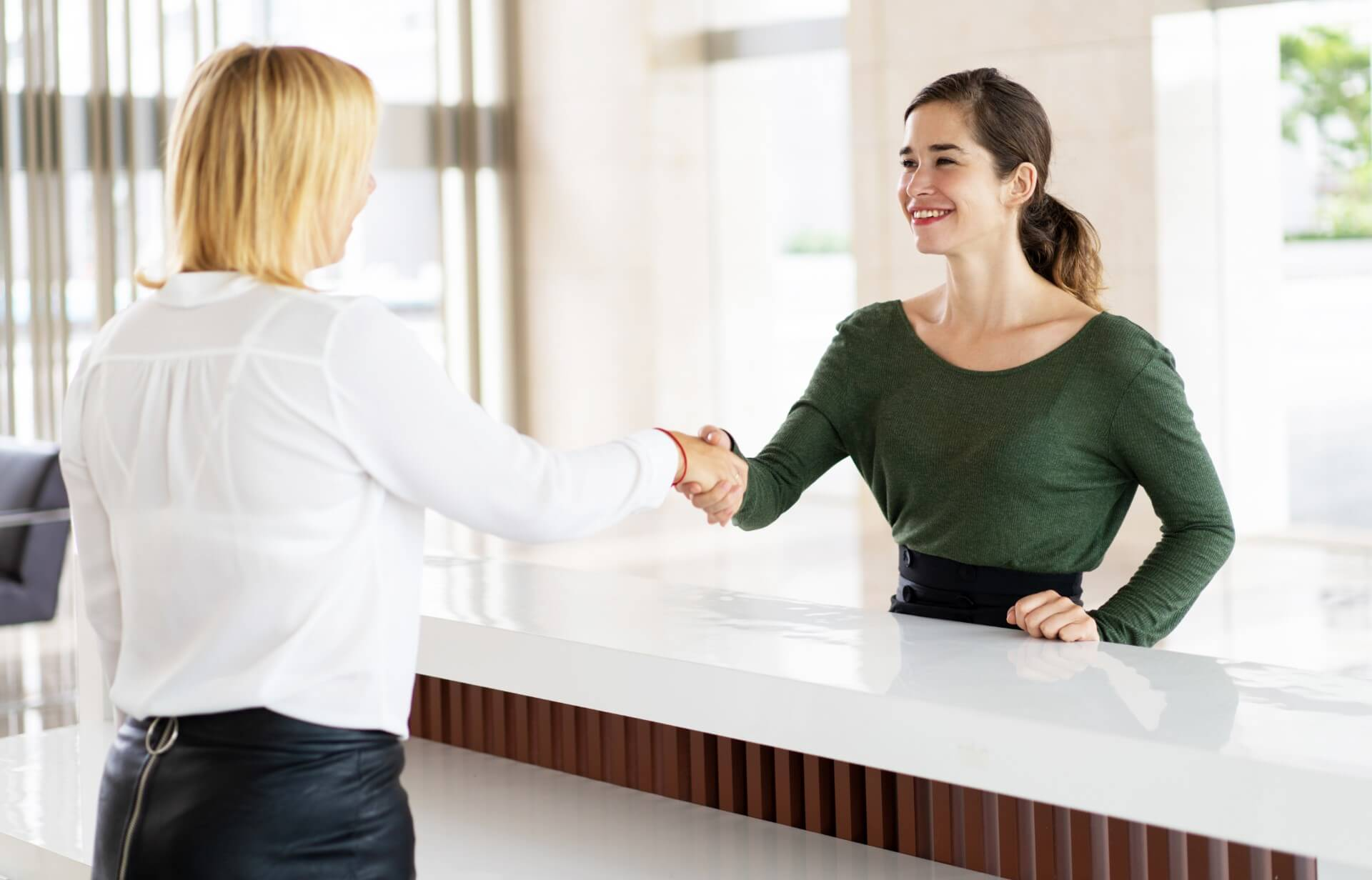 receptionist welcoming a guest with a handshake Επαγγελματικά Σεμινάρια Υπάλληλος Υποδοχής – Κρατήσεων Front Office Manager - Receptionist | Ξενοδοχειακό Πρόγραμμα Κρατήσεων PROTEL